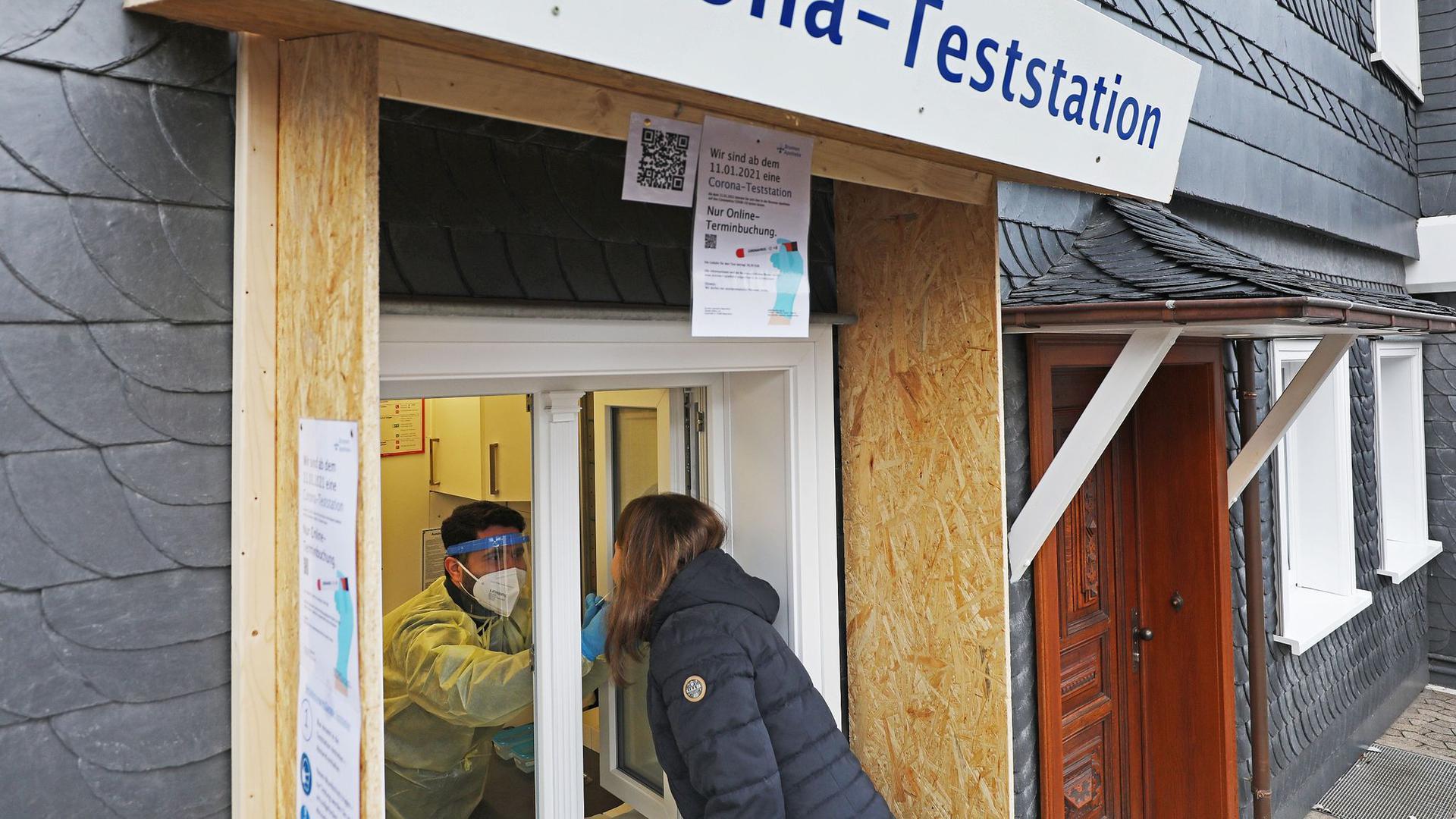 Ein Apotheker nimmt von einer Frau einen Abstrich an einer Corona-Teststation in Wipperfürth.
