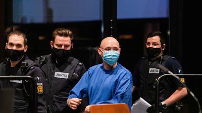 Der Angeklagte Yves R. wird von Justizbeamten in den Verhandlungssaal im Landgericht Offenburg geführt.