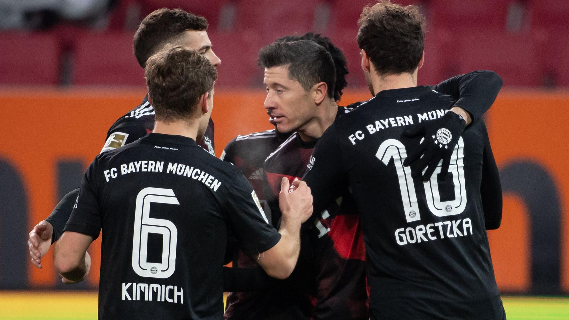 Der FC Bayern München setzte sich auch dank Torjäger Robert Lewandowski (M.) knapp in Augsburg durch.