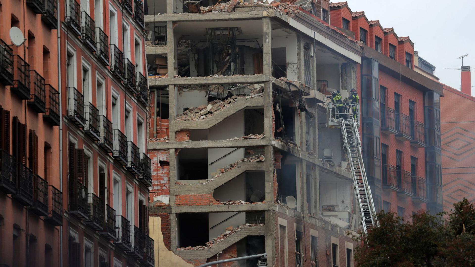 Feuerwehrleute arbeiten nach der schweren Explosion an dem beschädigten Gebäude in Madrids Toledo Straße.