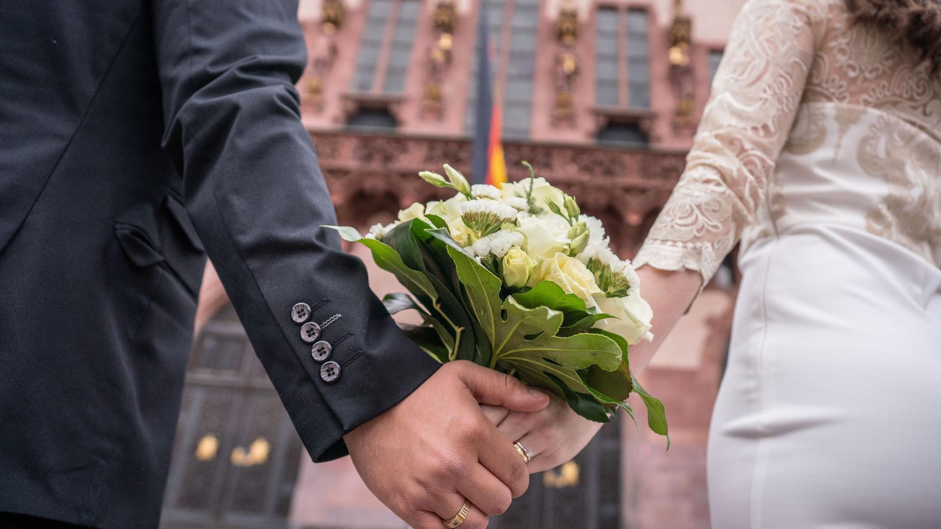 Ein Brautpaar steht nach der standesamtlichen Trauung auf dem Römerberg in Frankfurt.