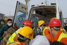Retter tragen einen Bergarbeiter zu einem Krankenwagen. Zwei Wochen nach einem Grubenunglück im Osten Chinas wurde er geborgen.