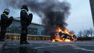Flammen schlagen aus einem Auto, das vor dem Bahnhof in Eindhoven auf dem Kopf liegt.