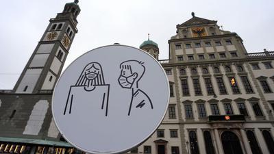 Ein Schild auf dem Rathausplatz in Augsburg weist auf Maskenpflicht hin.