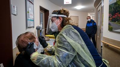 """Eine Altenpflegerin testet am Eingang zum DRK-Pflege- und Betreuungszentrum """"Tor zur Altstadt"""" in Sangerhausen eine Besucherin."""