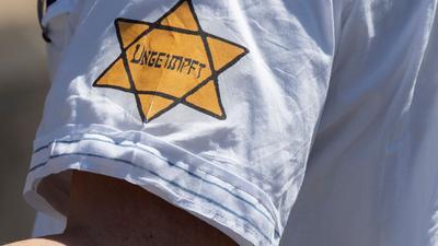 """""""Ungeimpft"""" steht auf einem nachgebildeten Judenstern am Arm eines Mannes, der versucht hatte, sich unter die Teilnehmer einer Demonstration in Frankfurt im Mai vergangenen Jahres zu mischen, die sich auch gegen Verschwörungstheorien zum Corona-Virus wendet."""