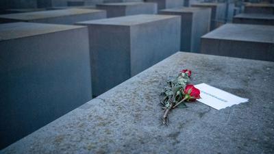 """Rosen liegen mit einem Zettel, mit der Aufschrift """"#weremeber"""" am Holocaust-Mahnmal in Berlin."""