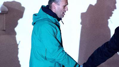 Alexej Nawalny, Oppositionspolitiker und Kremlkritiker, wird von einem Polizeibeamten eskortiert.