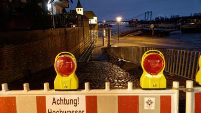 Ein Schild an einer Absperrung warnt vor Hochwasser, nachdem das Wasser des Rheins die Uferstraße in Rodenkirchen überflutet hat.