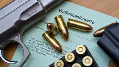 Eine Kaliber 9 mm Pistole, Patronen und ein Magazin liegen auf einer Waffenbesitzkarte.