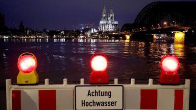 Eine Absperrung steht am Rheinufer. In Köln steigt der Pegelstand, für die Schifffahrt gibt es erste Einschränkungen.