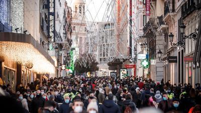 Zahlreiche Menschen mit Mund-Nasen-Schutz gehen eine Einkaufsstraße entlang.