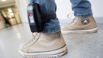 Der Sender sitzt in einem schwarzen Kunststoff-Kästchen am Knöchel: Ein Mann mit einer elektronischen Fußfessel.