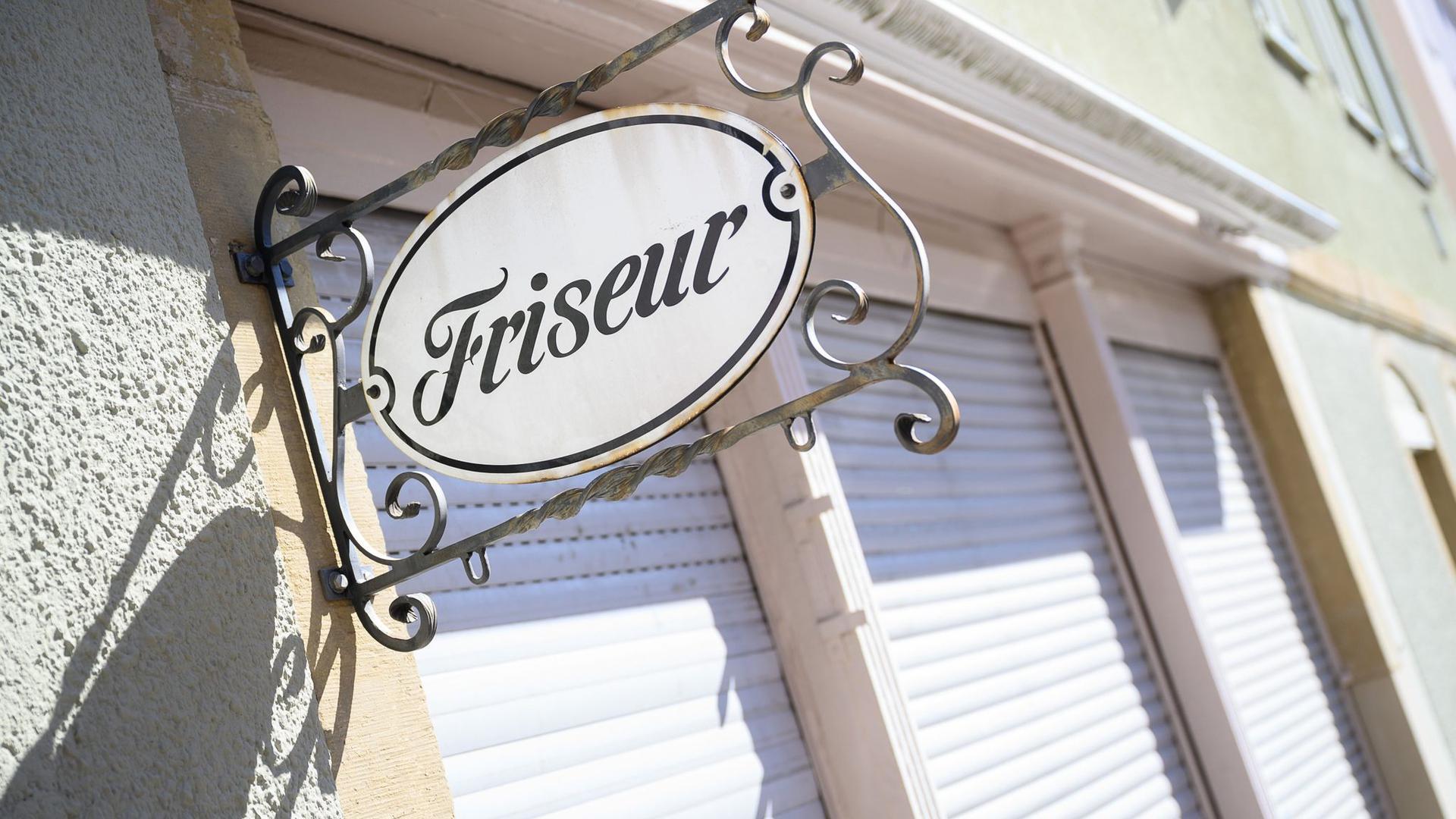 """Ein Schild mit der Aufschrift """"Friseur"""" hängt an einem geschlossenen Friseursalon. Dürfen die Friseure bald wieder Kunden empfangen?"""