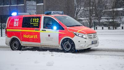 Ein Notarztwagen vom Rettungsdienst fährt mit Blaulicht auf einer zugeschneiten Straße in Bielefeld.