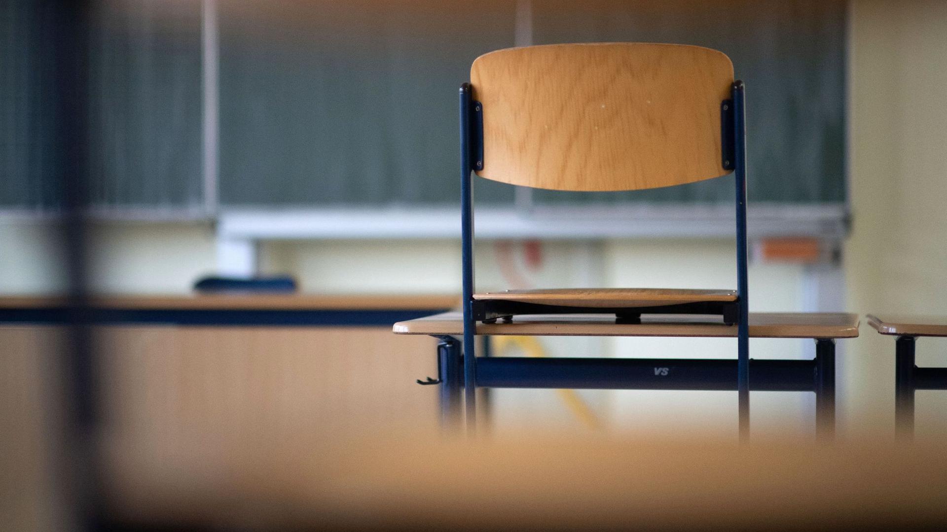 Ein Stuhl in einem Klassenzimmer auf einem Tisch. Wann sollen die Schulen öffnen?