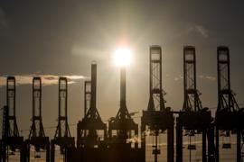Die Sonne scheint hinter den Kränen des Hamburger Containerterminals Burchardkai. Die Corona-Krise hat der deutschen Exportwirtschaft im vergangenen Jahr schwer zugesetzt.