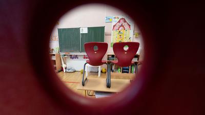 Stühle stehen in einem Klassenzimmer einer ersten Klasse der Marienschule inStuttgart auf Tischen.