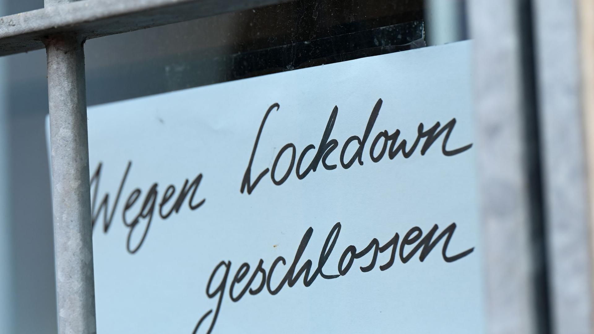 """Ein Zettel mit der Aufschrift """"Wegen Corona geschlossen"""" hängt am Schaufenster eines Geschäfts."""