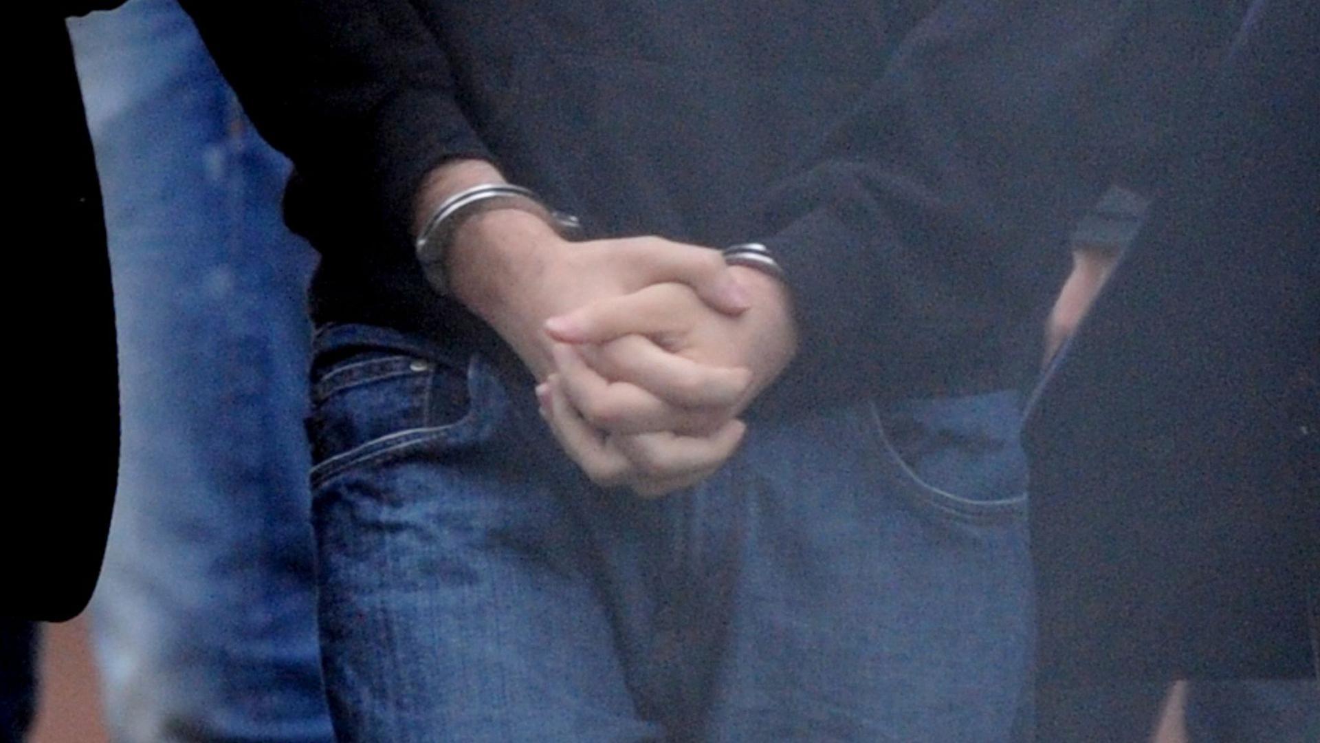 Die mit Handschellen gefesselten Hände eines mutmaßlichen Terroristen. (Symbolbild)