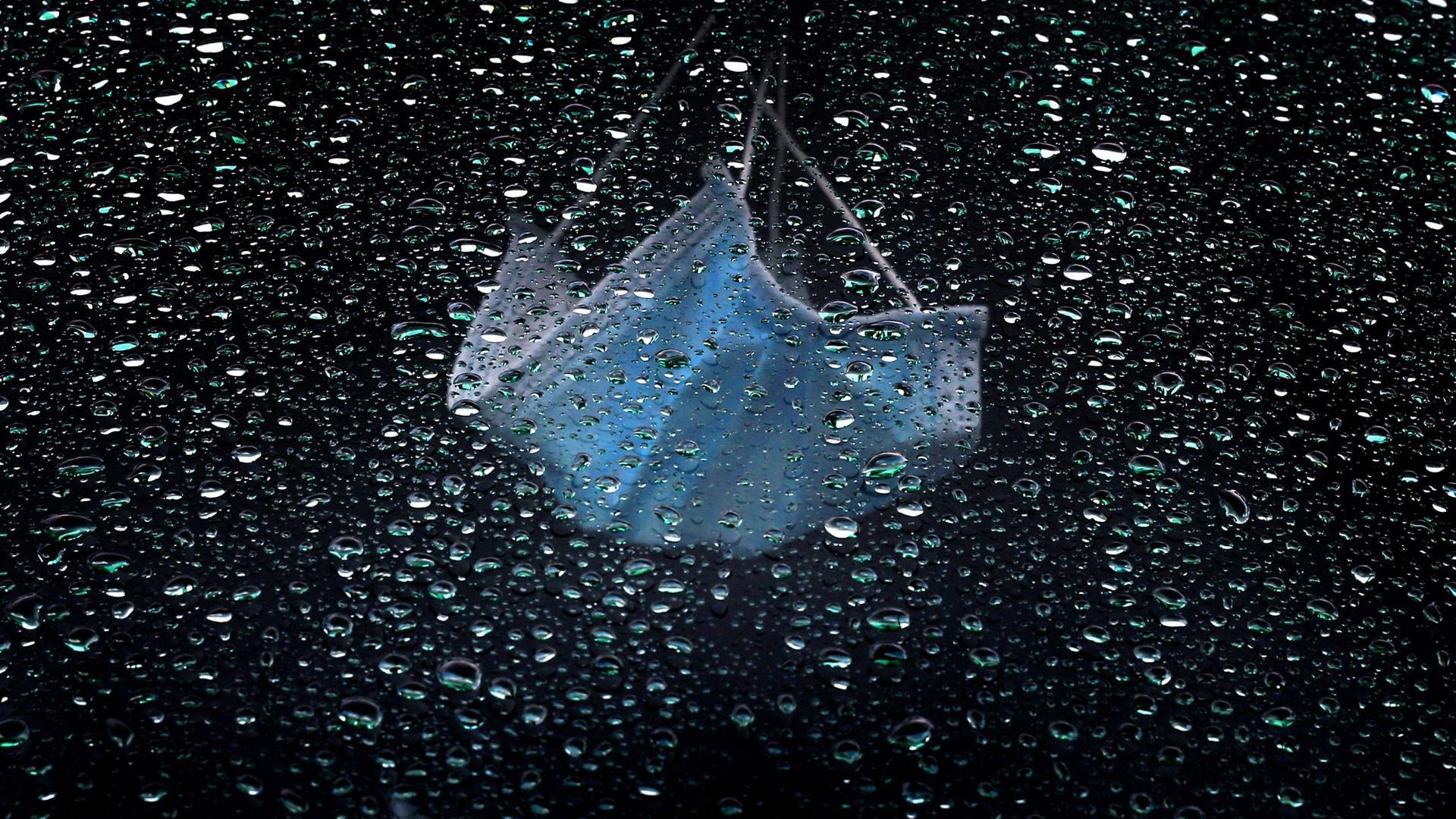 Ein medizinischer Mundschutz hängt am Rückspiegel eines im Regen parkenden Autos.
