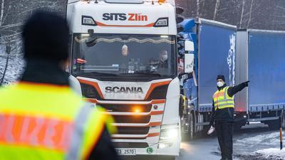 Polizisten kontrollieren auf einem Parkplatz kurz nach der deutsch-tschechischen Grenze Fahrzeuge.