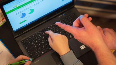 Ein Junge nutzt zusammen mit seinem Vater einen Laptop für den Heimunterricht.