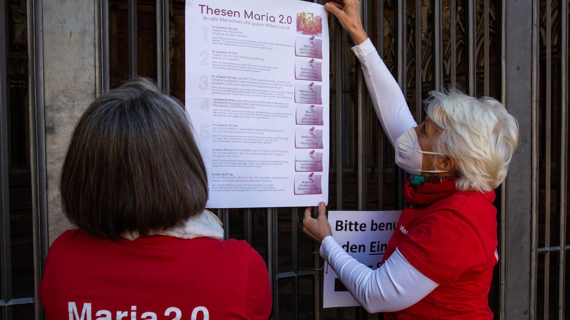 Zwei Aktivistinnen der katholischen Reforminitiative Maria 2.0 hängen ein Plakat mit ihren Thesen an das Hauptportal des Freiburger Münsters.