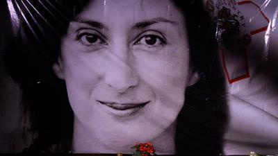Blumen und eine Kerze liegen vor einem Porträt der ermordeten Enthüllungsjournalistin Daphne Caruana Galizia in Valletta.