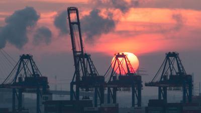 Sonnenuntergang hinter den Containerbrücken des HHLA Containerterminal Tollerort in Hamburg. Die Corona-Krise reißt tiefe Löcher in den Staatshaushalt.