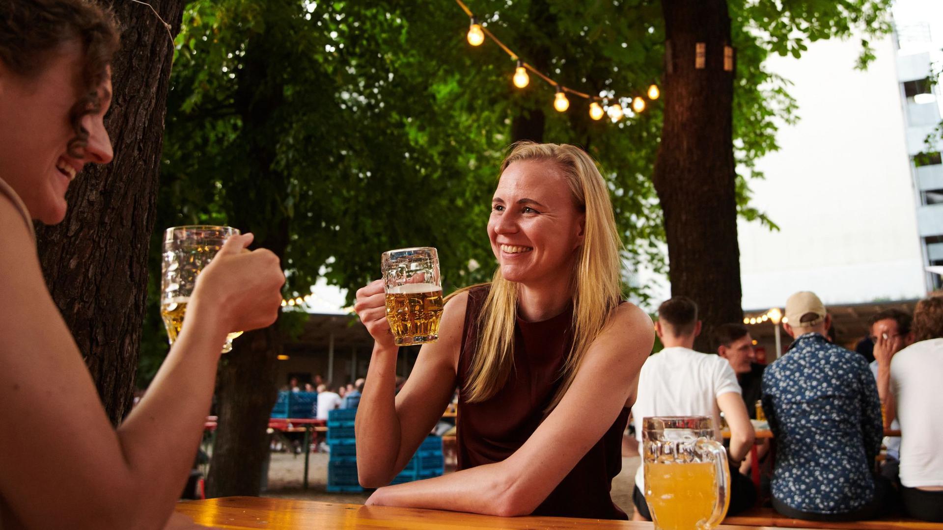 Zwei Frauen trinken ein Bier im Prater Biergarten in Berlin.