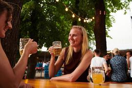 Zwei Frauen trinken ein Bier im Biergarten in Berlin.