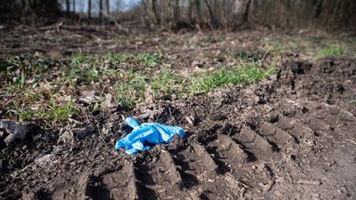 Ein Einmalhandschuh liegt nahe des mutmaßlichen Tatorts. Nachdem ein 13-jähriger Junge tot in der Nähe von Sinsheim gefunden worden ist, gehen die Ermittlungen der Polizei weiter.