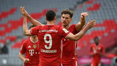 Münchens Robert Lewandowski (M) bejubelt sein Tor zum 2:0 mit Leon Goretzka.