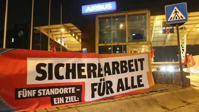 """Ein Transparent mit der Aufschrift """"Sichere Arbeit für Alle"""" hängt vor den Werkstoren des Flugzeugherstellers Airbus in Hamburg-Finkenwerder."""