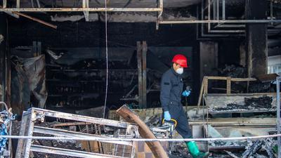 Ein Brandermittler der Polizei sucht drei Tage nach dem Brand eines türkischen Geschäfts nachSpuren.