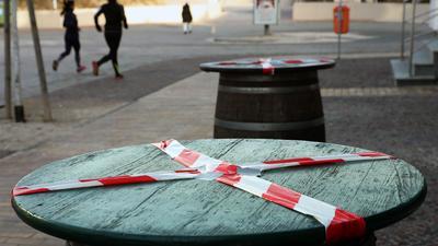 Kein gemütliches Beisammensein:Mit einem rot-weißen-Flatterband sind Stehtische an der Promenade des Ostseebades Warnemünde abgeklebt.