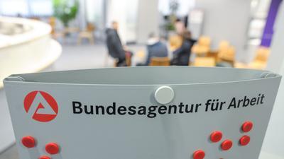 Mehrere Personen sitzen im Wartebereich der Bundesagentur für Arbeit in Stuttgart.