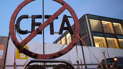 Ein durchgestrichenes Ceta-Symbol auf einem Anhänger von Greenpeace-Aktivisten vor dem Landtag in Stuttgart.