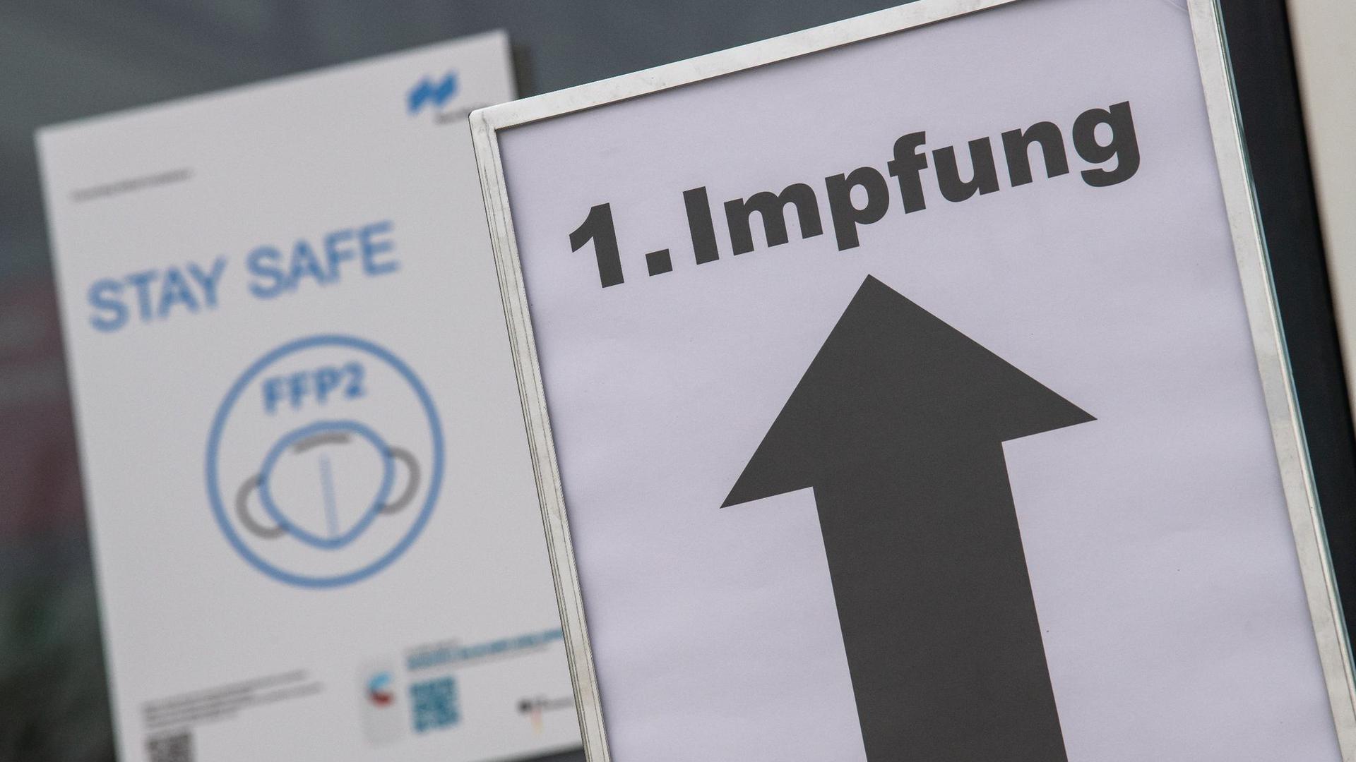 Ein Schild auf einemMessegelände weist den Weg zu einem Impfzentrum.