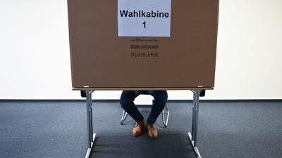 Ein Mann sitzt im Wahlraum des Briefwahllokals Frankfurt Innenstadt hinter einer Wahlkabine.