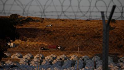 Ein Polizeiauto patrouilliert oberhalb eines provisorischen Zeltlagers für geflüchtete Menschen in der Nähe von Mytilini.