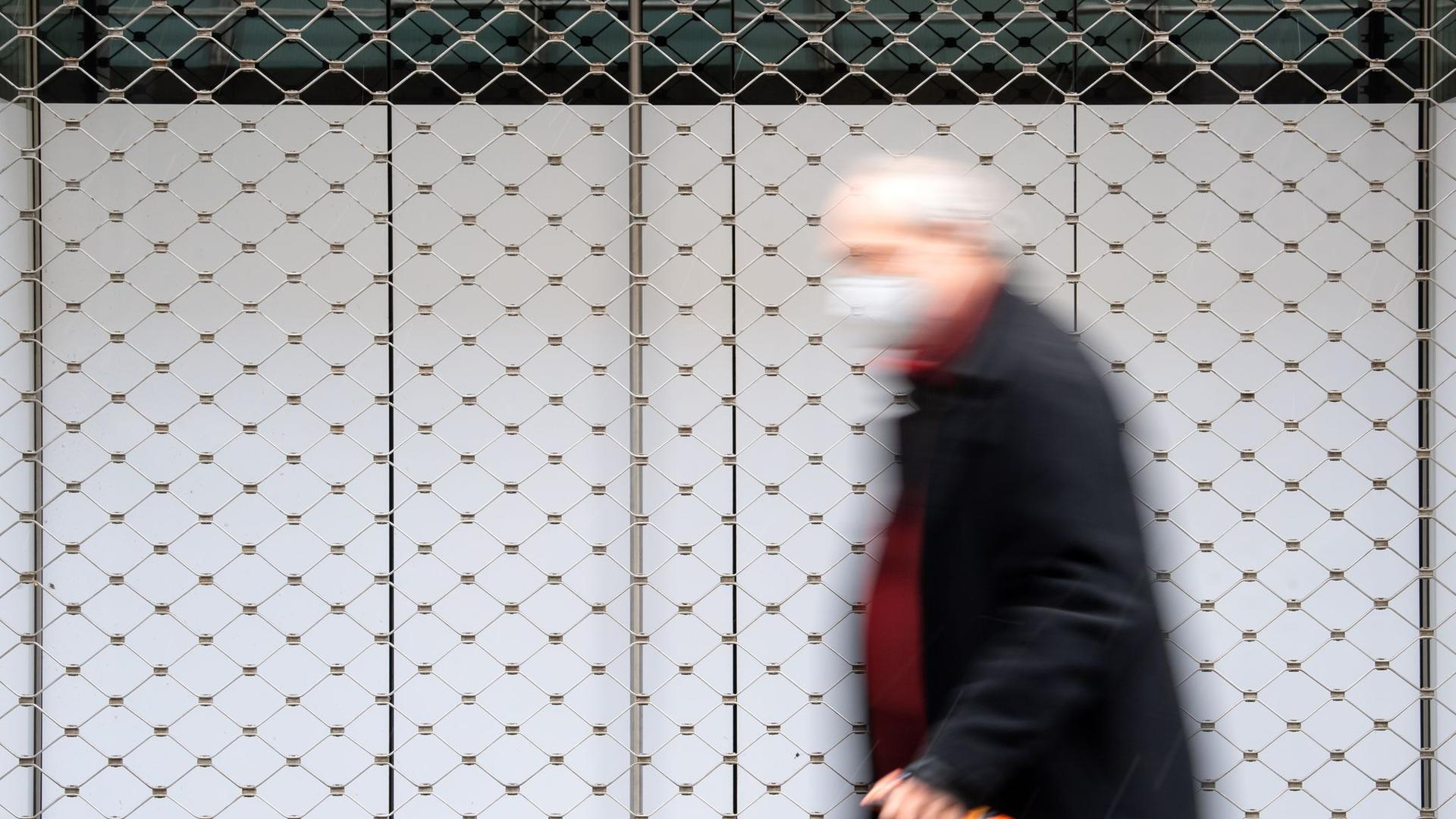 Ein Mann geht in einer Innenstadt an einem geschlossenen Geschäft vorbei.