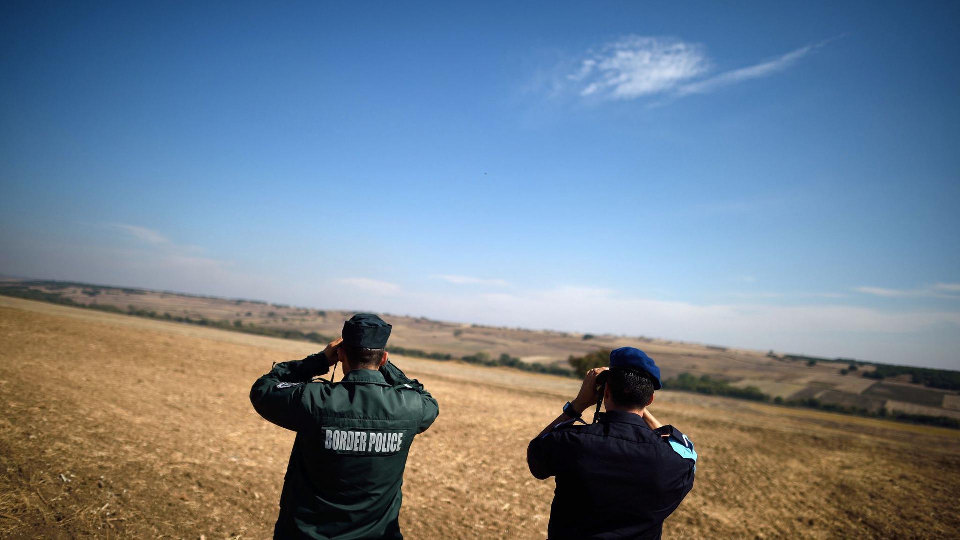 Zwei Beamte der europäischen Grenzschutzagentur Frontex aus Bulgarien (l) und den Niederlanden beobachten mit Ferngläsern die bulgarisch-türkische Grenze.