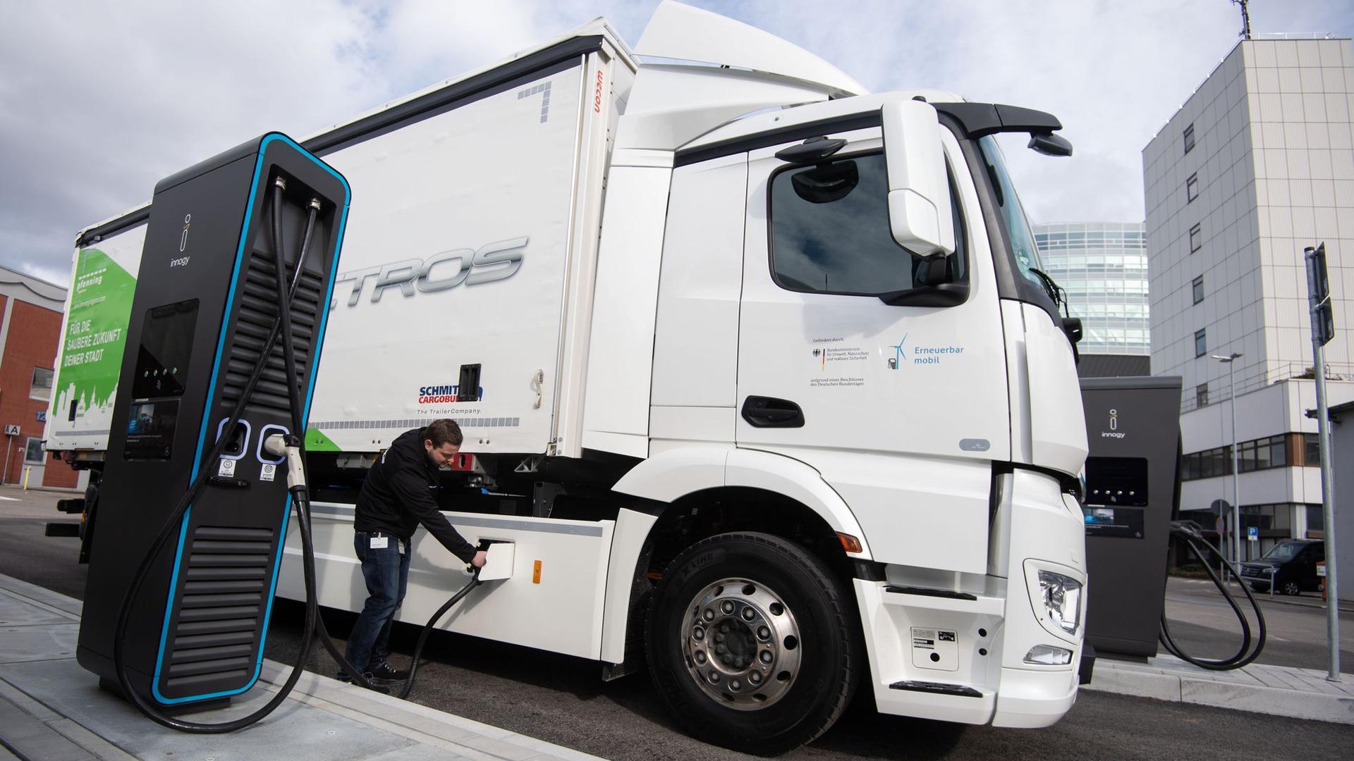 Ein Mitarbeiter der Daimler AG steckt einen Ladestecker in einen elektrisch angetriebenen Mercedes-Benz eActros.
