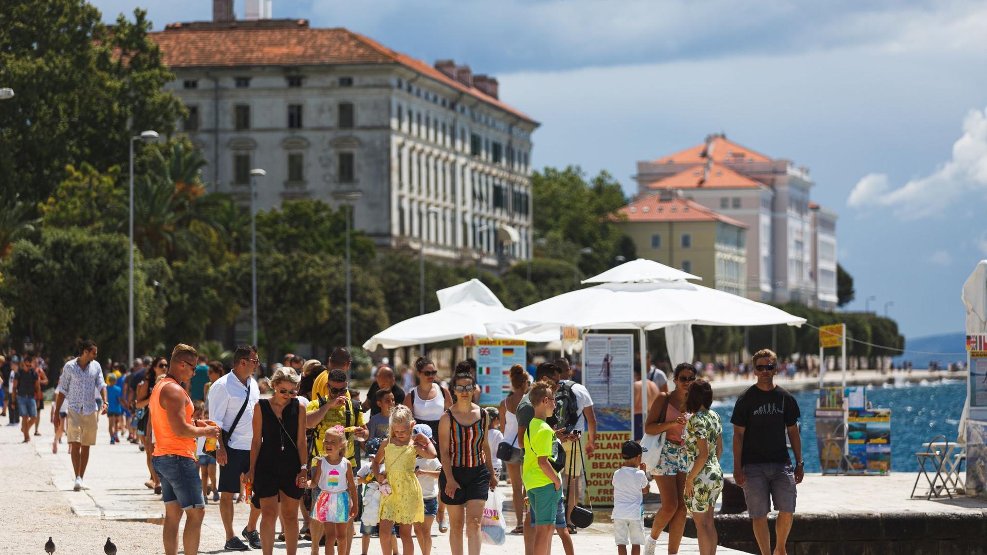 Touristen spazieren an der Uferpromenade in Zadar entlang. Ganz Kroatien gilt ab Samstag als Risikogebiet.