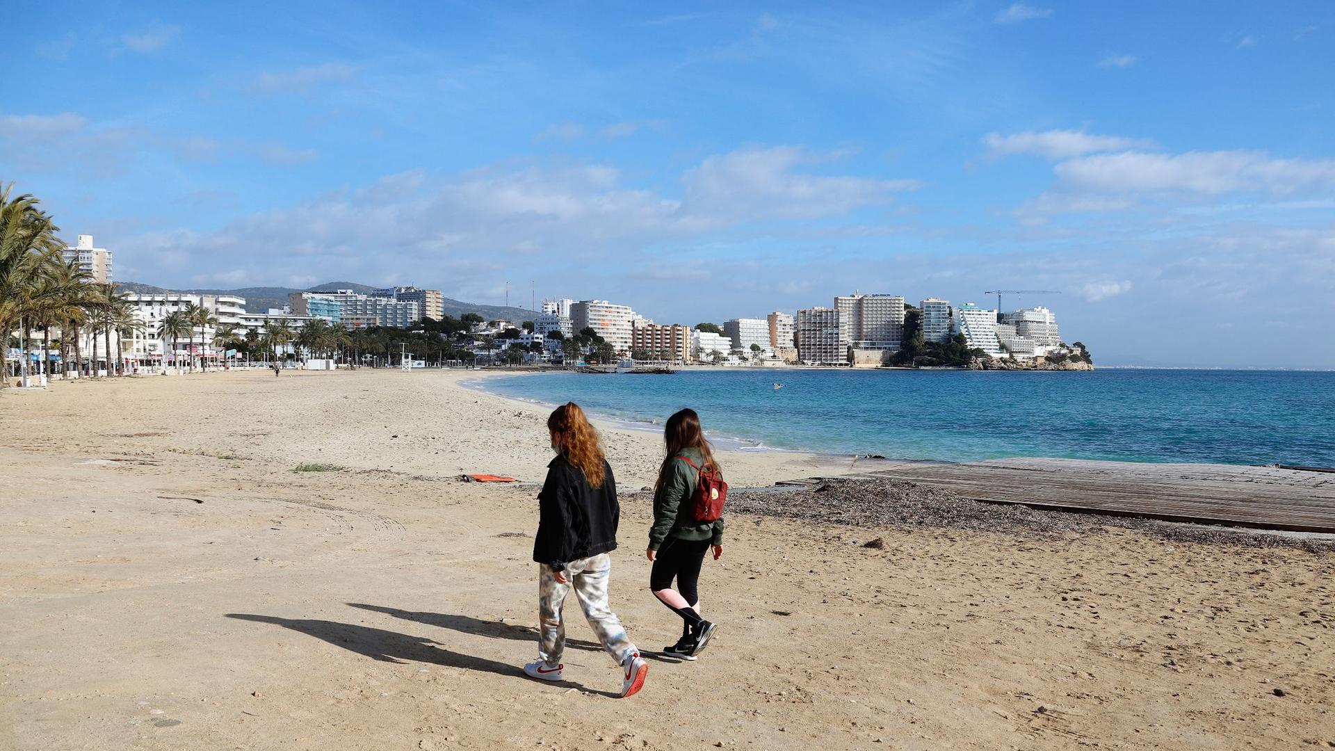 Zwei junge Frauen gehen am leeren Strand von Magaluf entlang.