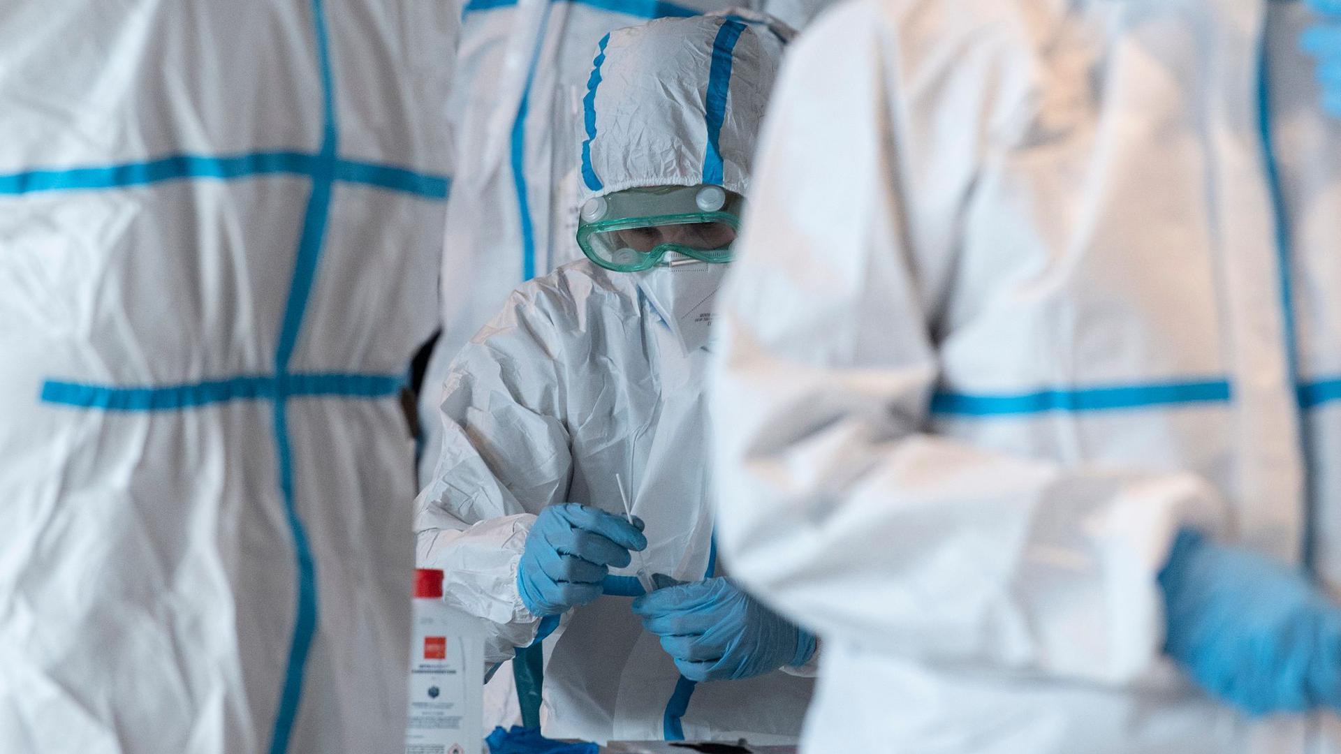 Mitarbeiter mit Schutzanzügen in einem Corona-Testzentrum.