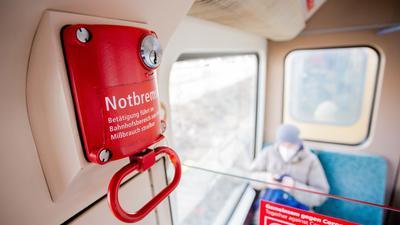 Ein Fahrgast mit Mund-Nasen-Schutz sitzt in einer Berliner S-Bahn hinter der Notbremse.