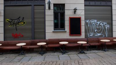 Leere Tische und Bänke stehen vor einer Kneipe in der Altstadt von Halle/Saale. Die Politik ringt um eine bundesweite Corona-Notbremse.